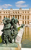 Three ornamental cherubs are at one of the corners of a pond in the Versailles gardens.