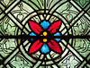 A detail from a staned glass window in the cathedral of Notre Dame in Paris. The decoration features a red and blue pattern surrounded by grape vines.