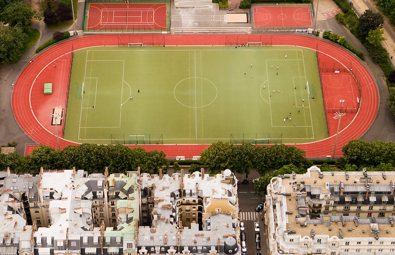 A French football (or soccer) field as seen from the Eiffel Tower above. A game is in progress with players on the field.