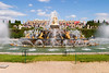 A view of the palace of Versailles from the Fountain of Latona which is one of the main ornamental fountains in the gardens. Streams of water are spraying over the sculptures.