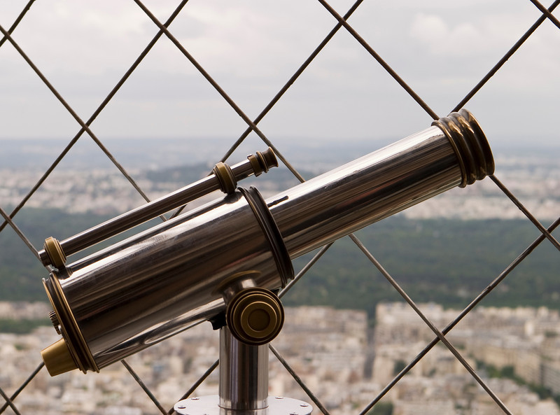 A shiny telescope on the observation deck of the Effel Tower is outlined against a background of the security fence and the Paris city skyline.
