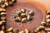 Chestnuts being roasted on an rusty iron brazier in Paris outside the Louvre. The shells are cracked and the meat inside is ready to be eaten.