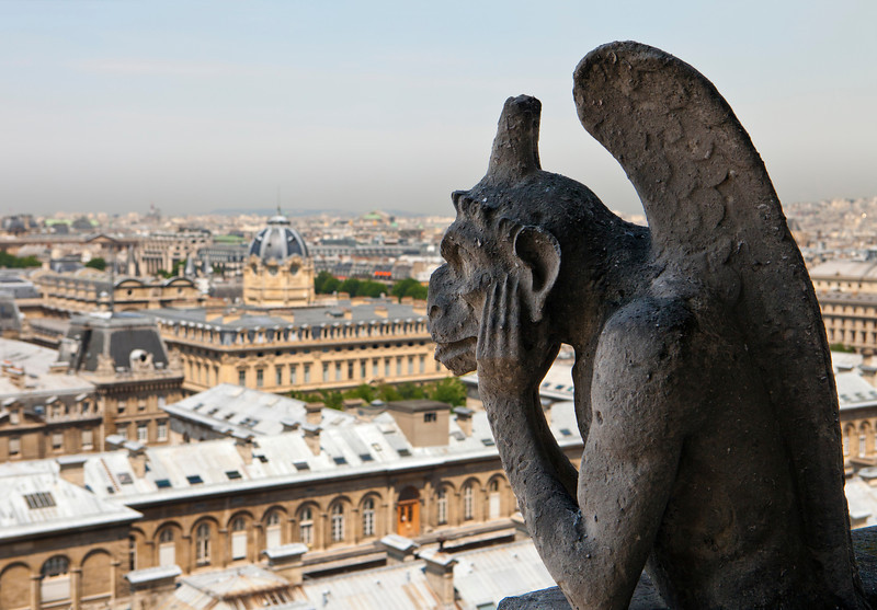 Stone carving of a French gargoyle is looking over the city of Paris while thinking and holding its head in its hands.