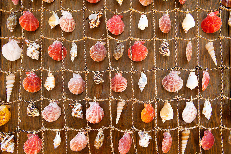 A tapestry or wall hanging is made of brightly colored sea shells and knotted into a net as seen in Heraklion, Crete.