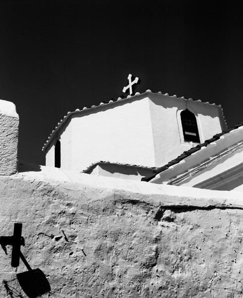 A small Greek Orthodox church in Lindos on the island of Rhodes viewed from one of the narrow allies. The cross on the top is miirrored by the shadow in the lower left corner. (Scanned from black and white film.)