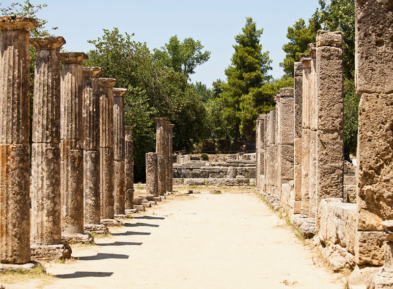 Two rows of old stone pillars stand on either side of a common area in the ruins of the ancient Greek city of Olympia.