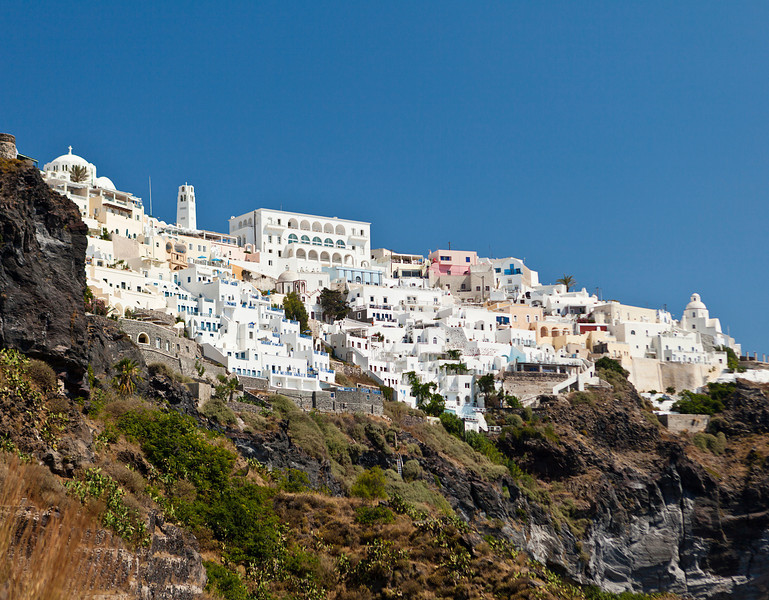 A view of the town of Thera on the Greek island of Santorini. The city of white buildings is built along the crater rim of an old volcano.
