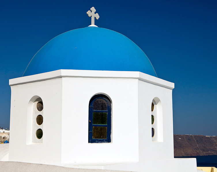 Classic view of one of the Greek Orthodox churches with the blue dome and cross outlined against the sky.