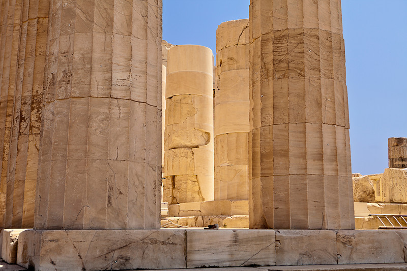 A detail view of a set of pillars at the Parthenon in Athens glowing with reflections of the white marble in the mid-day light.