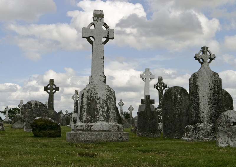 A historic old cemetery in Ireland with Gaelic headstones showing the traditional cross in a circle. Clonmacnoise is situated in County Offaly, Ireland on the River Shannon. The original church and monastery was built in 545 by Saint Ciarán.