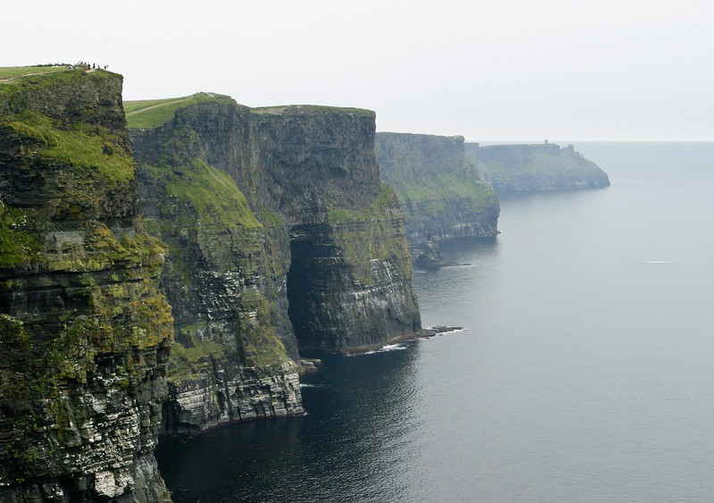 The dark, ominous Cliffs of Moher are a landmark in Western Ireland with sheer rock walls that rise 600 feet from the ocean. A small crowd of people in the field at the upper left provide a sense of scale.