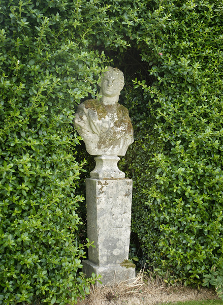 An old, weathered statue located in a garden alcove, surrounded by a large hedge.