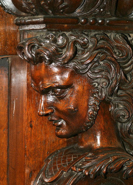 A detailed element of a decorative carved wood figure used as support for a fireplace mantel in the Irish Parliament House in Dublin, Ireland.