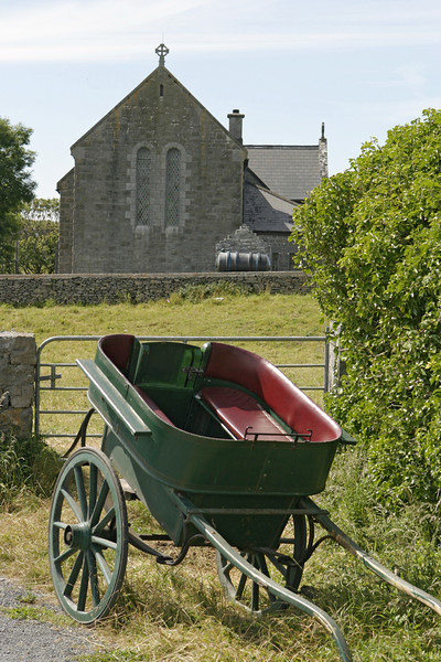 A horse-drawn carrage is standing in front of a church on the Aran Islands while the horse is likely grazing elsewhere. This traditional and timeless means of transportation is still used on the island although mostly for tourists.