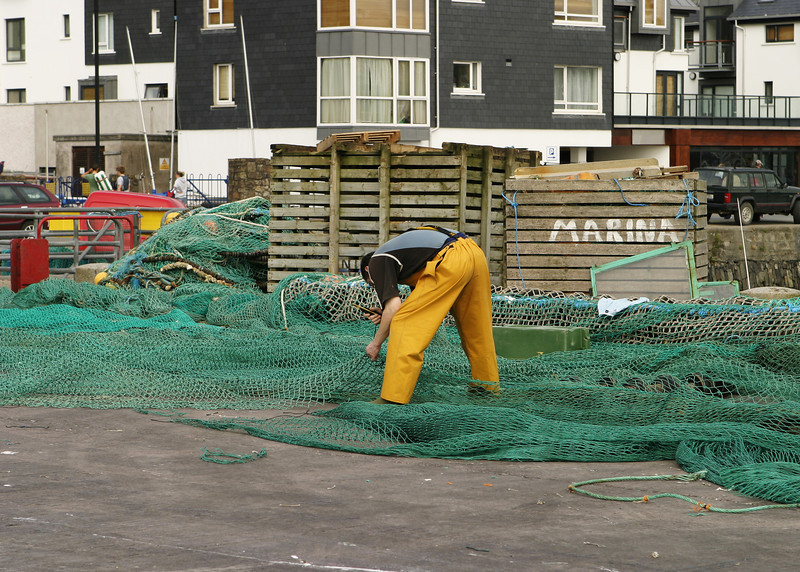 A fisherman in yellow overalls is leaning over as he repairs his fish nets after bringing in his catch for the day.