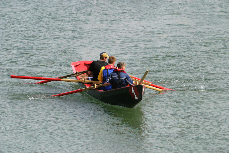 Three young Irish men rowing in the boat races in the Aran Islands. They are not quite in unison as they pull on their red oars but they're having fun anyway.