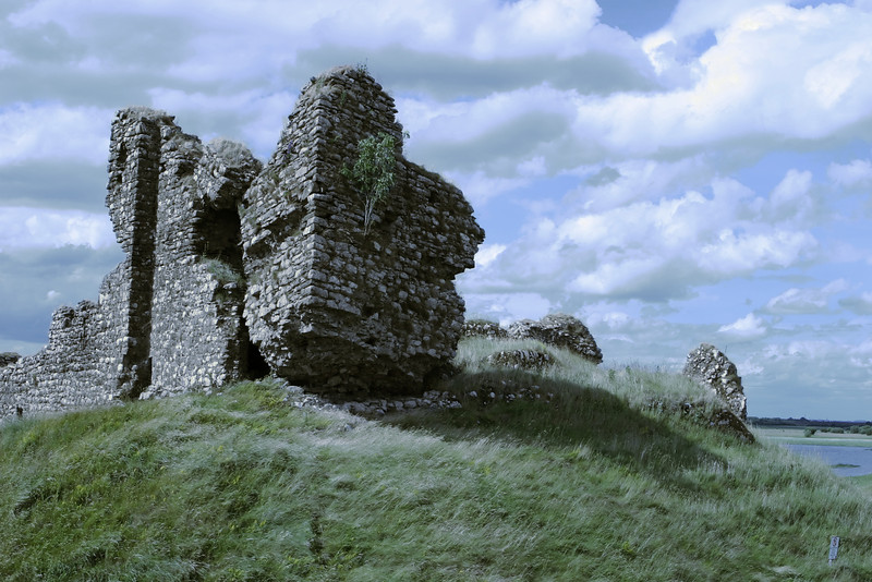 An ancient castle in ruins. This travel scene from Ireland is typical of many medieval buildings that have been gradually demolished over time.