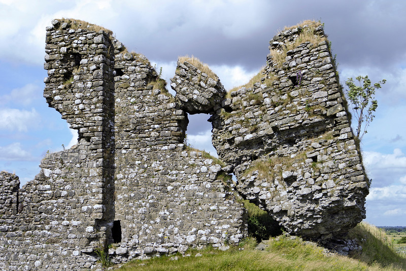 The ruined facade of Clonmacnoise Castle in County Offaly, Ireland. The ruins show elements of the old stone walls tilting on a little knoll or hill in the country.