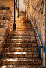 A narrow stone staircase rises through the back alleys of Zefat with a bit of glow on the limestone. Zefat is a historic town in Isreal, known for its mysticism and the scholarship of the people who studied there.