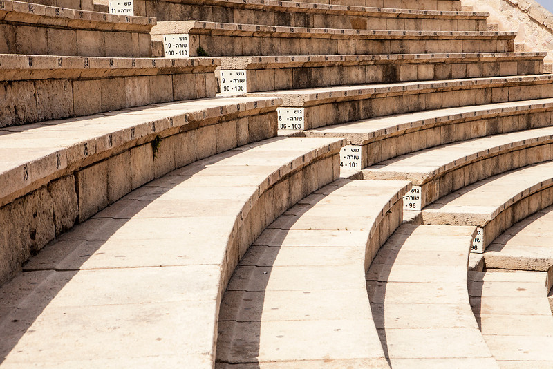The Roman theater at Caesaria in Israel has been restored and is now used for modern performances. The tiered rows of seating provide a clean, repetitive pattern that arcs into the distance.