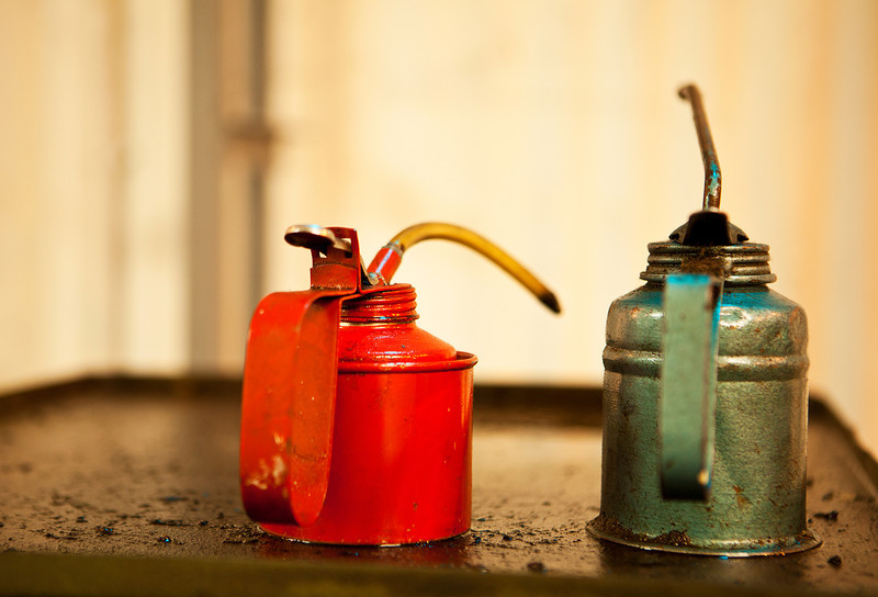 Two cans of machine oil, one red and one green, rest on top of an old piece of greasy machinery that was used to make ammunition at the Ayalon Institute in Israel.