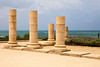 A set of stone pillars standing near the coast at the ancient Roman city of Caesaria in Israel. The stones glow against the gloomy skies in the background.