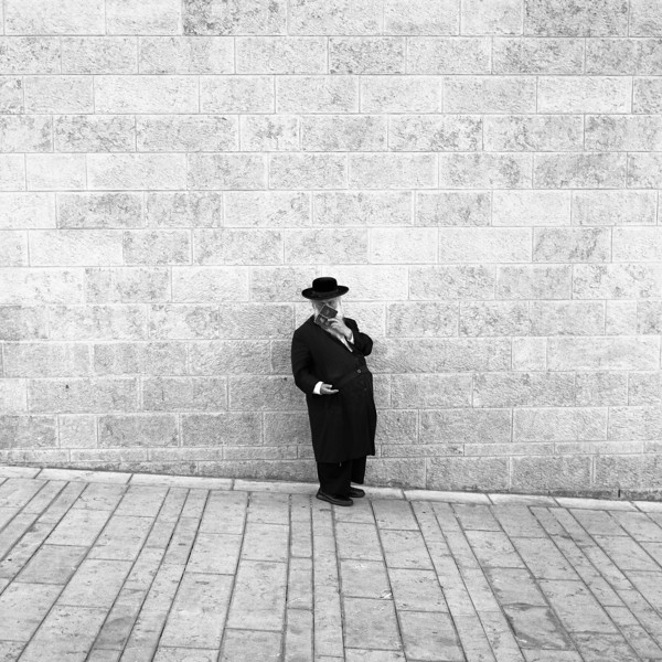 A lone man peering out at the world while appearing to read a small book of prayer on the ramp leading to the Western Wall in Jerusalem.