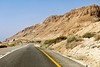 With the Dead Sea Mountains on the right, a two-lane highway twists through the desert.