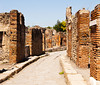 A narrow street in Pompeii winds between old brick walls of ancient homes in a residential area.