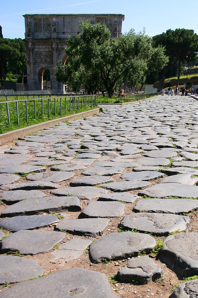 An ancient roman road, worn down to just a set of polished old cobblestones, leads past the Roman Forum to the Arch of Constantine.