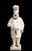 A statue of an plump Italian chef (capo or cucinare) stands in sunshine in Italy as a symbol to the restaurant behind. Isolated to a black background.