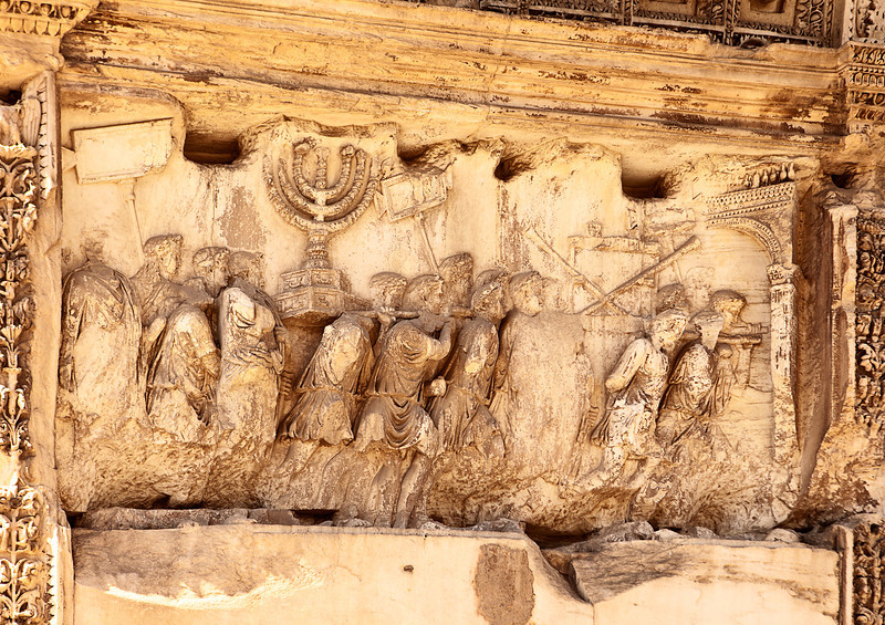 This wall relief on the Arch of Titus reveals Roman soldiers carrying spoils from the destruction of the Temple of Jerusalem in 70 A.D including the golden Temple Menorah, the Table of the Shewbread and the silver trumpets which called Jews to the festivals. The Romans are in triumphal procession wearing laurel crowns and the ones carrying the Menorah have pillows on their shoulders.
