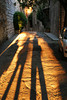 A set of long shadows from three people, taken just before sundown, looking along a street in Assisi. The golden glow of a Tuscan sunset (or, could be morning) gives this image a warm, romantic feeling.