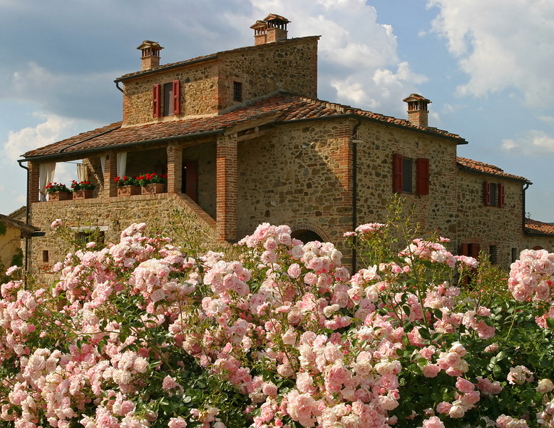 A typical Italian country villa in Tuscany during the summer. This old building was fronted by a wonderful flower garden which is shown in the foreground.