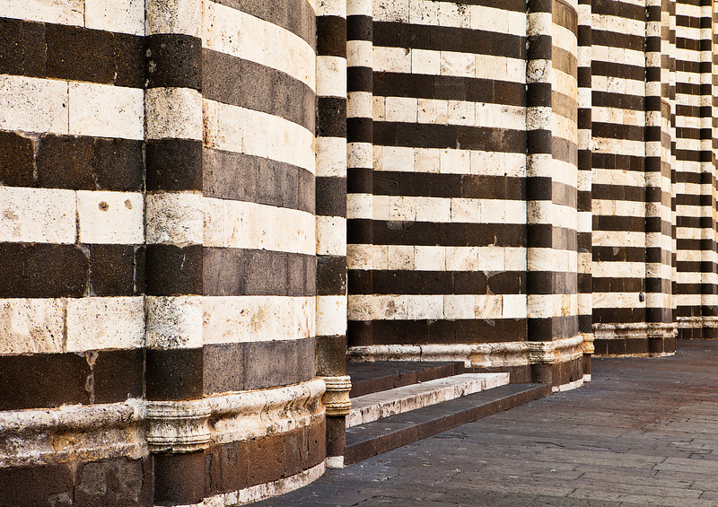 An architectural detail view of the alternating pattern of black and white stone layers used as the exterior facade of the main cathedral, or Duomo, in Orvieto, Italy.