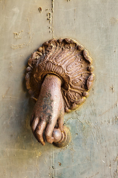A mysterious hand comes out of the door to hold a knocker. This rusty ornamental fixture was seen on a door in Orvieto, Italy.