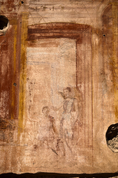 A detail section of one of the remaining fresco paintings on plaster in the Pompeii architectural site. This appears to show a man and a boy standing inside a building's entrance.