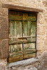 A rough-hewn and weathered cellar door in the hill town of Civita in Umbria, Italy. The green paint on the wooden door is peeling and faded.