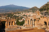 A view from high up in the cheap seats in the ancient Roman theatre or Teatro Antico of Taormino in Sicily shows the city and then the cone of the Mt. Etna volcano in the distance.