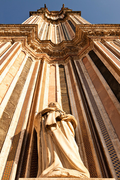 A view looking upwards to the top of one of the twin belltowers of the main cathedral, the Duomo, in Orvieto. The extreme perspective foreshortens the tower.