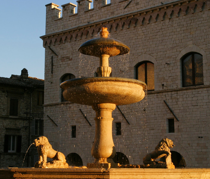 An old Italian fountain in the main town square of Assissi. Droplets of water from the fountain are highlighted in the warm golden glow of the evening just before sunset.
