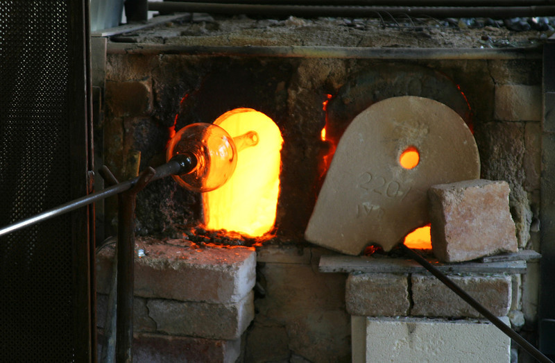 An artisan's furnace in a small Venetian studio where they are blowing a glass vase. The bright orange furnace is heating to over 1,000 degrees to melt the glass.