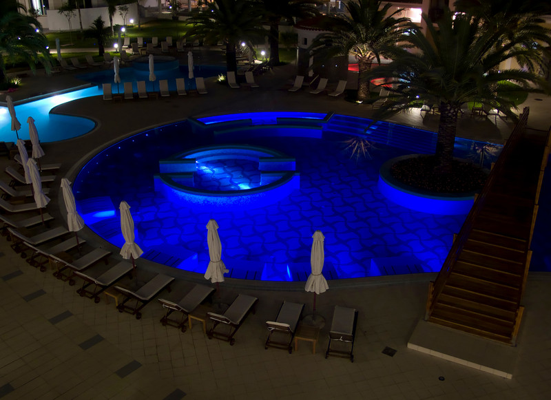 A swimming pool at night is illuminated to a luminescent type of sapphire blue color.