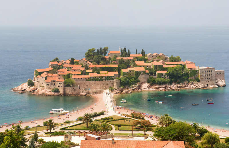 A large-scale view of the Sveti Stefan peninsula in Montenegro taken from an overlook off the local highway. The horizon is obscured by the haze.