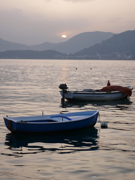 Two fishing boats in a Montenegro harbor are nearly silhoutted by the sun which is about to go behind a distant mountain range.