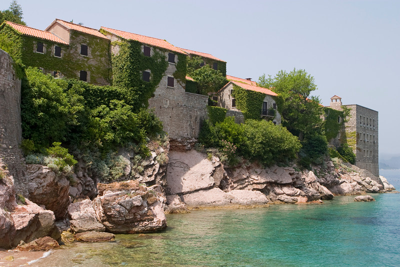 Part of the resort island of Sveti Stefan showing the old buildings on top of the cliffs at the water's edge.