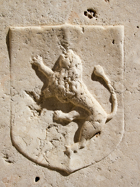 A lion on a shield is carved into a slab of white marble. The shadow helps provide some contrast.
