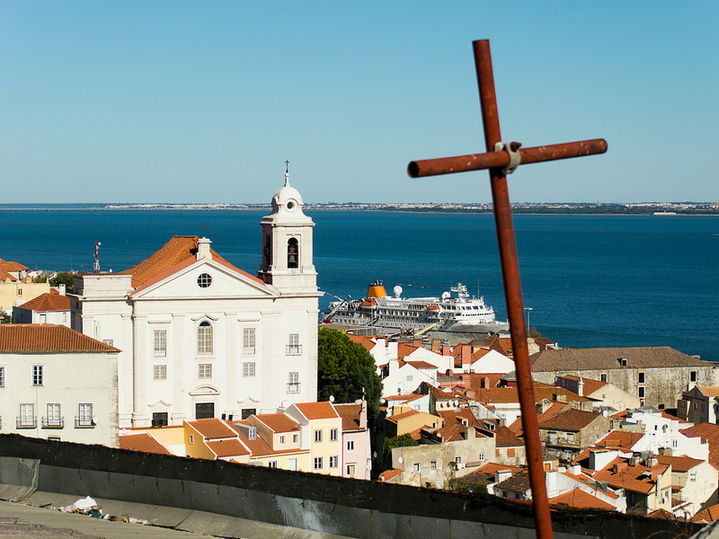 A view of Santo Estevao church in the Alfama barrio and the Tagus River in Lisbon, Portugal. In the foreground, an iron cross is an unused grapevine trellis.