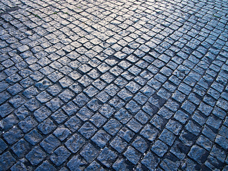 Square cobblestones, slightly polished from traffic, show a reflection from the sun at dusk on a street in the Alfama district of Lisbon.