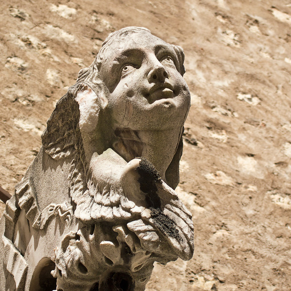 A stone carving of an angel in white marble is highlighted against an old mortar wall of a church in Lisbon, Portugal.